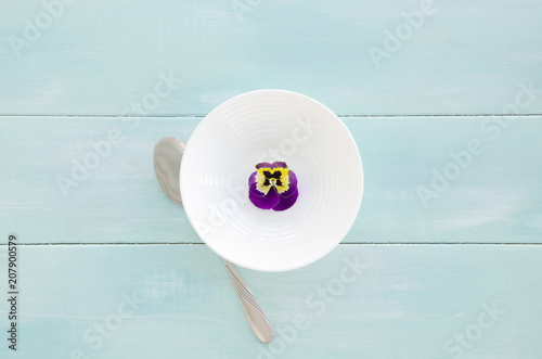 Staande foto Pansies White bowl with pansy flower on mint wooden background