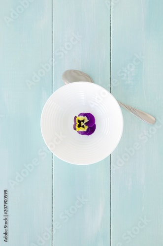 Spoed Foto op Canvas Pansies White bowl with pansy flower on mint wooden background