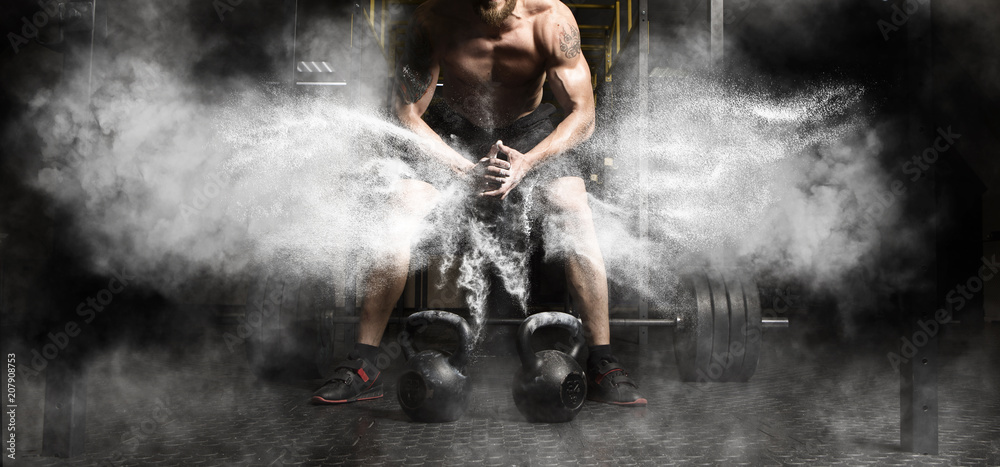 Fototapeta Muscular man workout with kettlebell at gym