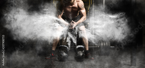 Photo Stands Fitness Muscular man workout with kettlebell at gym