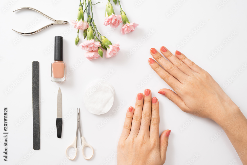 Fototapety, obrazy: Female hands applying purple nail polish on wooden table with towel and nail set