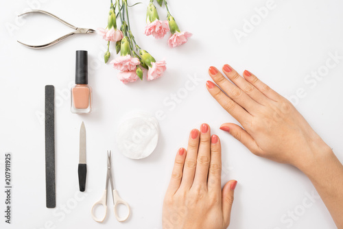 Deurstickers Manicure Female hands applying purple nail polish on wooden table with towel and nail set