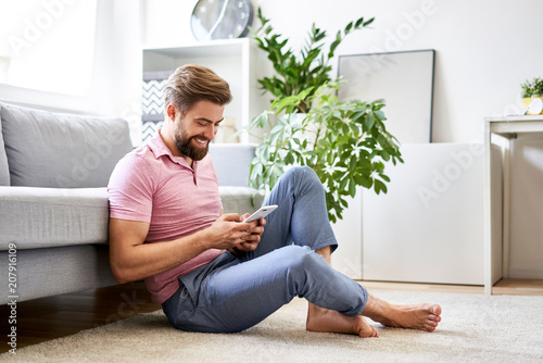 Fotografía  Happy, relaxed man at home using phone sitting on the floor