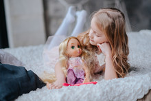 Adorable Toddler Girl With Blond Curly Hair Playing Indoors With Doll