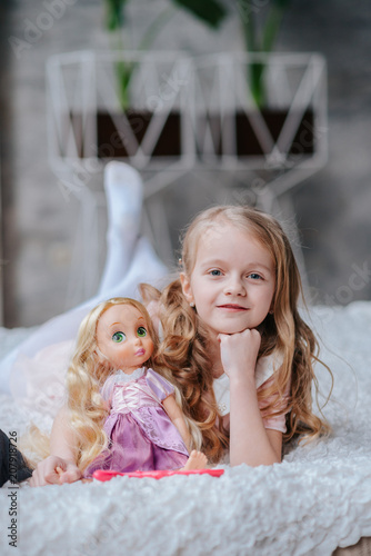 Adorable toddler girl with blond curly hair playing indoors with doll Poster Mural XXL