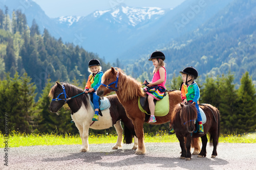 Poster Horseback riding Kids riding pony. Child on horse in Alps mountains