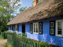Old Blue Cottage With A Straw Roof And White Windows