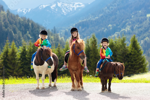 Kids riding pony. Child on horse in Alps mountains Wallpaper Mural