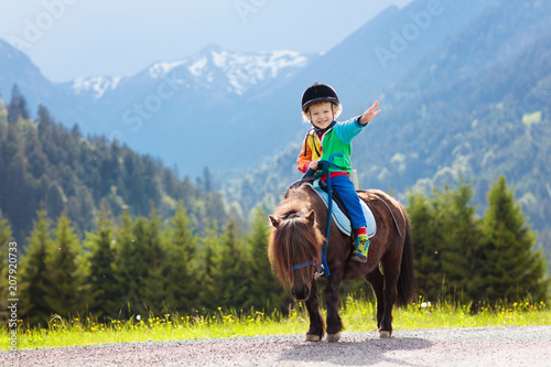 Poster Equitation Kids riding pony. Child on horse in Alps mountains