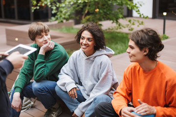 Smiling lady with dark curly hair sitting with her friends in courtyard of university. Group of cool students spending time together