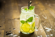 Cold Fresh Lemonade Mojito Cocktail With Ice, Lemon And Mint Leaves In Mason Jar On Rustic Dark Wooden Background. Summer Concept.