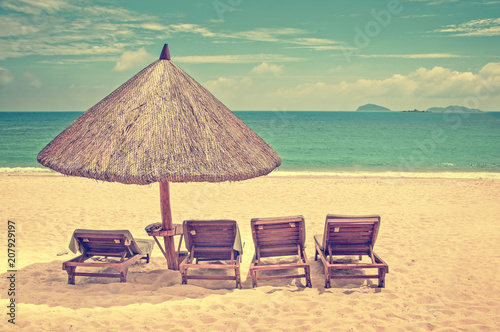 Straw Beach Umbrella And Wooden Reclining Chairs On A Perfect Vintage Process
