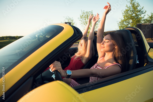 Close up picture of the two lovely charming girls with closed eyes lifting  up theirs arms 1a7edbb9e0eb5