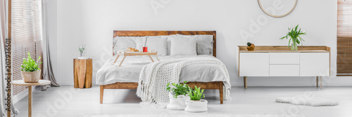 Panorama of a bright white and wooden bedroom interior with double bed and sideboard Tablou Canvas