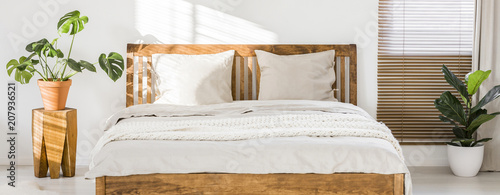 Fényképezés Close-up of double wooden bed with bedding, pillows and blanket against white wall in a bright sunny bedroom interior