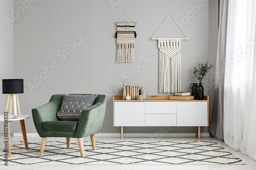 Foto op Canvas Restaurant Green armchair on patterned carpet near table with lamp in minimal living room interior. Real photo