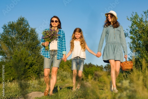 Fotografia, Obraz  Mother and daughter hold hands, walk along the country road.