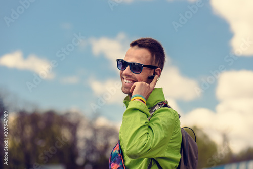 Photo Smiling happy tourist talking on phone with bluetooth headset device