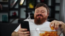 Fat Man Smiles While He Reads Something In His Smartphone And Eats Potato Chips