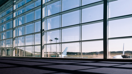 Walkway and glass curtain wall with Airplane background at Airport terminal, Travel concept with copy space. Silhouette background