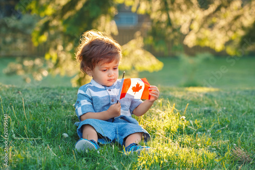 Spoed Foto op Canvas Canada portrait of little white Caucasian baby boy holding and looking at Canadian flag with red maple leaf. Toddler celebrating national Canada day sitting on grass in summer park outside