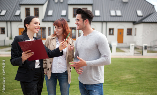 Fotografía  Young couple with real estate agent visiting house for sale in residential area