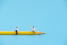 Miniature People Sitting On A Pencil