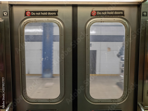 Fotografie, Obraz  Windows of a moving subway train looking out into station platform upon departur