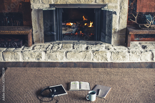 Cuadros en Lienzo Wide shot of open Bible, coffee, notepad and tablet in front of fire place