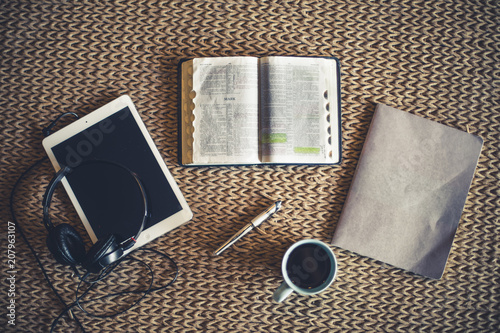 Photo Shot from above of open Bible, coffee, notepad and tablet in front of fire place
