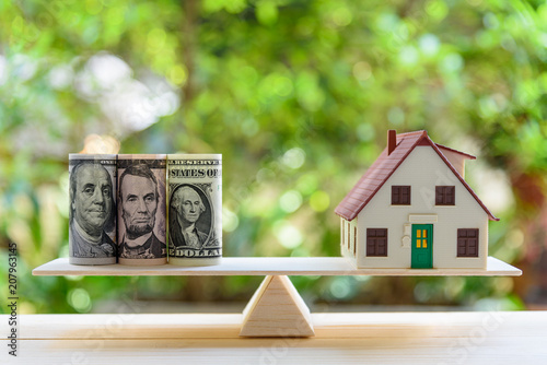 Fototapeta Home loan / reverse mortgage or transforming assets into cash concept : House model, US dollar notes on a simple balance scale, depicts a homeowner or a borrower turns properties / residence into cash obraz