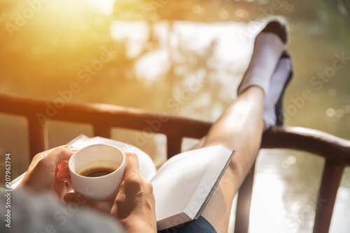 Obraz Happy Woman sitting and holding cup of hot coffee. - fototapety do salonu