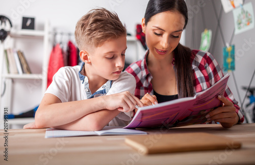Fotografia Mother helping her son with homework in teenage room at home