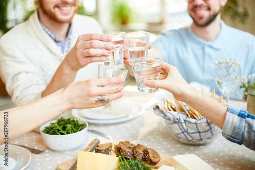 Crop blur view of friends sitting at serving table and clinking glasses with water celebrating event in cafe
