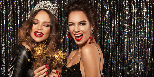 Two beautiful young girls smile, laugh and hold the Bengal lights, meet Christmas and New Year Wallpaper Mural