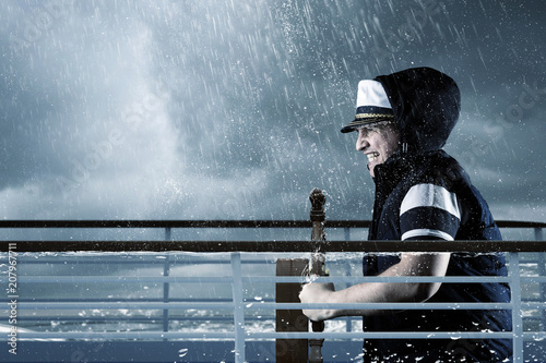 Fotografía  helmsman with vest and cap struggle against storm in front of stormy sea