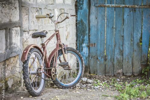 Foto auf AluDibond Old rusty children's bike near a blue door in the garden