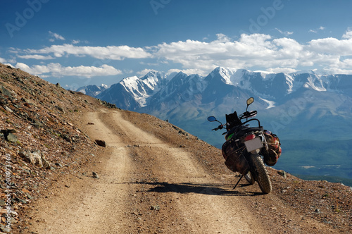 Motorcycle enduro traveler with suitcases standing alone on yellow stone extreme road path on the background of  high snow glacier ranges Altai mountains Siberia Russia