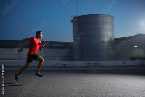 Young african american athlete running fast on the industrial street of a city at night