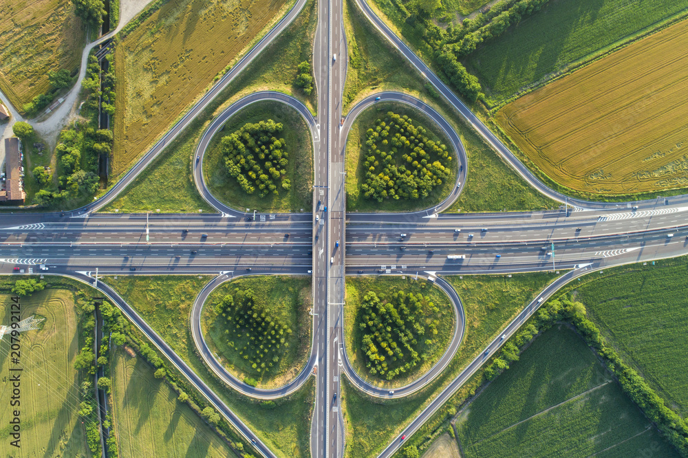 Fototapety, obrazy: Cloverleaf interchange seen from above. Aerial view of highway road junction in the countryside with trees and cultivated fields. Bird's eye view.