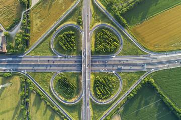 Wymiana koniczyny widziana z góry. Widok z lotu ptaka skrzyżowania autostrad na wsi z drzewami i polami uprawnymi. Widok z lotu ptaka.