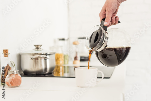 Photo cropped image of man pouring coffee into cup from coffee maker at kitchen