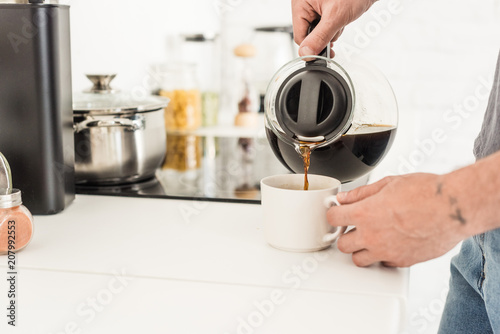 partial view of man pouring coffee into cup from coffee maker at kitchen Canvas Print