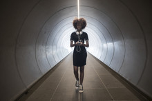 A Young Woman With Headphones Walking Through An Underground Passage