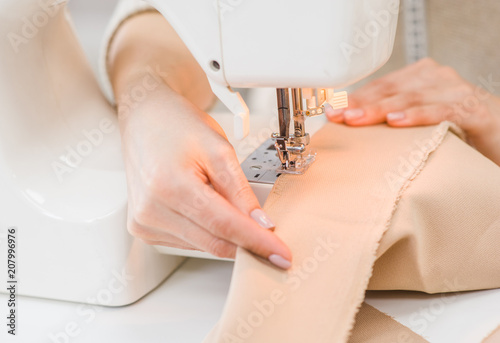 Dressmaker hand using sewing machine