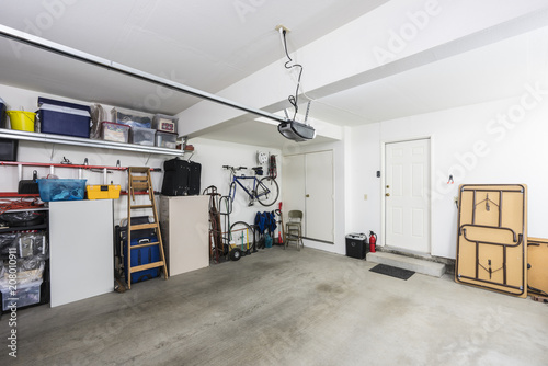 Photo Clean organized suburban residential two car garage with tools, file cabinets and sports equipment