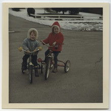 Brother And Sister In Winter Coats On Tricycles Outdoors In Vintage Family Photo
