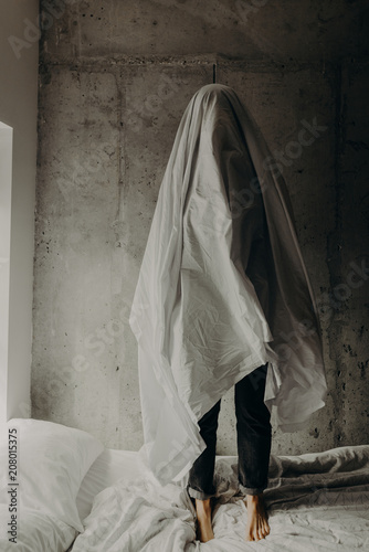 A sad ghost standing alone on a messy bed in a cement loft bedroom