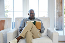 Senior Man Relaxing In Living Room While Reading A Book