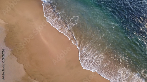 View from drone to shoreline - wave rolling back into the ocean leaving wet sand